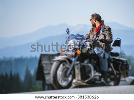 Brutal biker with beard in sunglasses, blue jeans and a leather jacket sitting on the travel motorbike and looking to the mountains. Sunny day in the mountains. Tilt shift soft effect