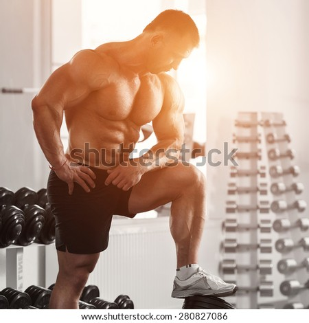 Brutal bodybuilder man of European appearance, is preparing to workout with dumbbells in the gym against the bright sunlight - stock photo