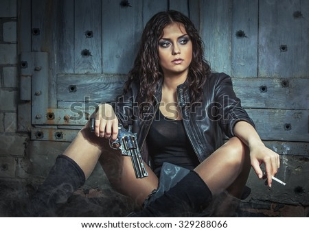 Brutal Girl with big gun, smoking. - stock photo
