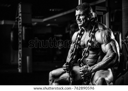 Brutal handsome Caucasian bodybuilder working out training in the gym with chain gaining weight pumping up muscles and poses fitness and bodybuilding concept