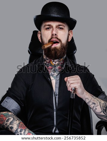 Brutal handsome man with tattooed body and cigar in his mouth sitting on chair - stock photo