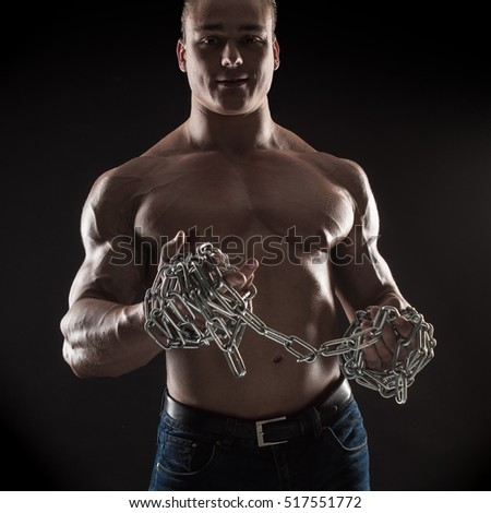 brutal man bodybuilder athlete holding a chain on a black background