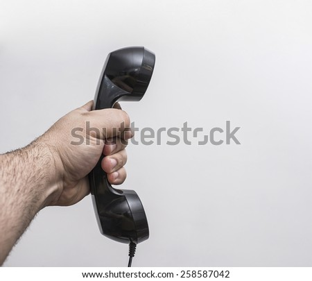 brutal man Hand with black plastic old retro vintage new telephone handset isolated on gray background Empty space for inscription or objects  - stock photo