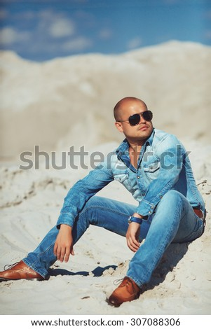 brutal man sitting on the sand, bronzed