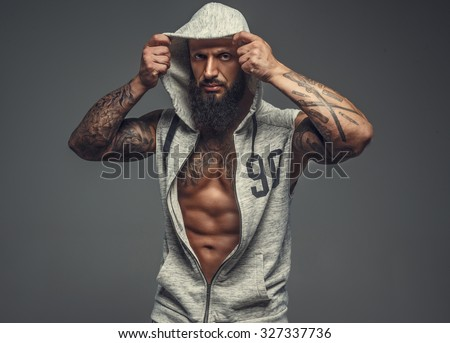 Brutal muscular tattooed gay in grey sports costume with hood on his head. Isolated on grey background.
