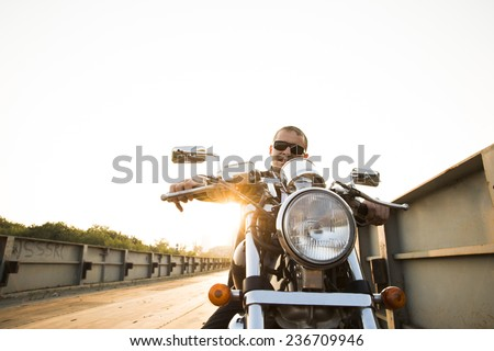 Brutal portrait handsome biker man in sunglasses sits on a bike on a sunset on old rusty metal bridge in city against house and sunny sky background Empty copy space for inscription - stock photo