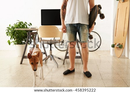Brutal tattoooed man in blank t-shirt holds surf skateboard in big loft in front of his working desktop with computer while his basenji dog curiously looking forward Vintage bike parked on back. - stock photo