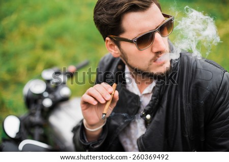 Brutal young guy in sunglasses Smoking a cigar while sitting on a motorcycle on the street and smoke - stock photo