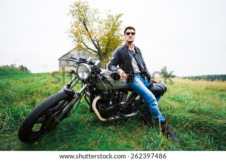 Brutal young man in sunglasses, blue jeans and a black leather jacket sitting on the custom motorcycle on the field near the building with a black helmet - stock photo
