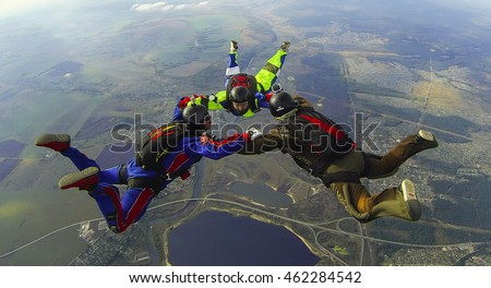 "BRYANSK/RUSSIA - OCTOBER 4,, 2015:  A group of three skydivers make a ""ring"" formation in the air"