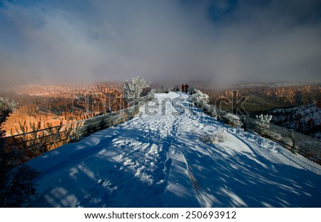 Bryce canyon panorama with snow and fog in Winter with red rocks and blue sky. - stock photo