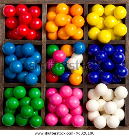 Bubble gum sorted into colors in a printers box 8 different colors - stock photo