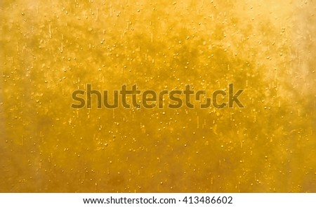 Bubbles floating in the liquid yellow drink, abstract image. - stock photo
