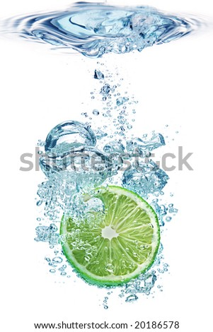 Bubbles forming in blue water after lime is dropped into it. - stock photo