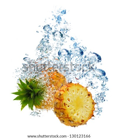 Bubbles forming in blue water after pineapple is dropped into it. - stock photo