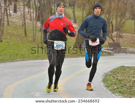 BUCHAREST, ROMANIA - DECEMBER 1st: Two unidentified marathon runners compete while snowing, at the National Day of Romania Marathon 2014, December 1st, 2014 in Bucharest, Romania - stock photo