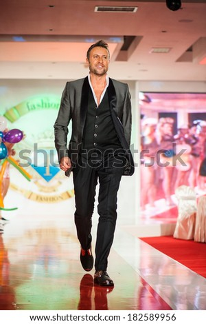 BUCHAREST, ROMANIA - DECEMBER 3: The designer Catalin Botezatu wear chlotes made by him, in Bucharest Fashion Week on December 3, 2012, Bucharest, Romania - stock photo