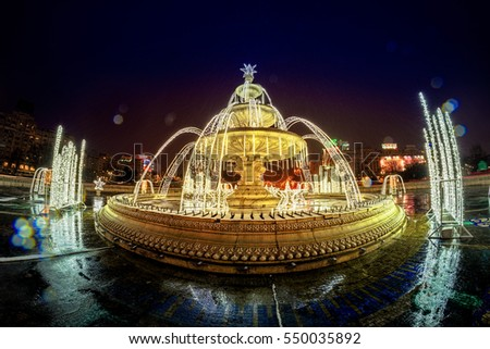 BUCHAREST, ROMANIA - DECEMBER 30, 2016: Union Square Fountain And House Of The People Or Parliament Palace (Casa Poporului) View From Union Boulevard (Bulevardul Unirii). Christmas lights.
