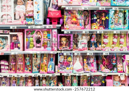 BUCHAREST, ROMANIA - FEBRUARY 28, 2015: Barbie Toys For Girls And Other Baby Toys On Supermarket Stand. - stock photo