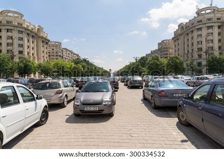 BUCHAREST, ROMANIA - JULY 26, 2015: Cars In Car Parking Lot In Front Of Parliament Palace (Casa Poporului) Or House Of The People In Bucharest. - stock photo