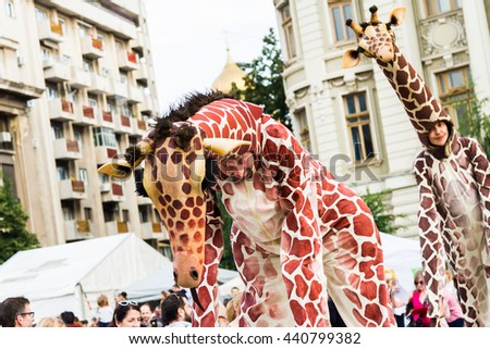 "BUCHAREST, ROMANIA - JUNE 09, 2016: Giraffes (Spain) present itinerant show inside of International Festival of Street Theater, ""B-FIT in the street 2016"" - stock photo"