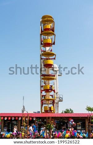 BUCHAREST, ROMANIA - JUNE 08, 2014: People Riding Giant Ferris Wheel In Youths Public Amusement Park (Tineretului Park) On Summer Day. - stock photo