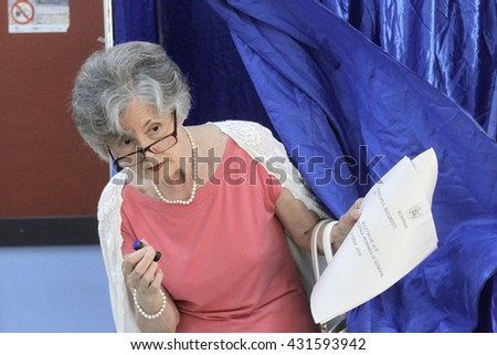 BUCHAREST, ROMANIA -June 05, 2016: Woman exit polling booth during the local elections. - stock photo