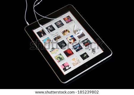 BUCHAREST, ROMANIA - MARCH 30, 2014: Photo of an ipad with earphones showing albums covers in the music player