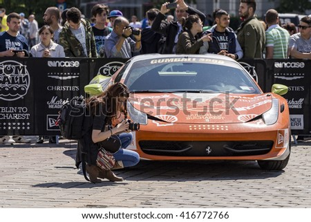 BUCHAREST, ROMANIA - MAY 7: Photographer and Ferrari 458 behind on May 7, 2016 in Bucharest. The car is part of the Gumball 3000 Dublin to Bucharest Charity Grid Rally. - stock photo