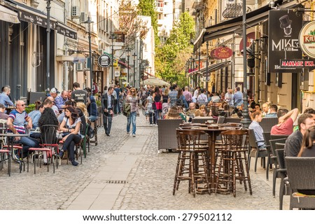 BUCHAREST, ROMANIA - MAY 18, 2015: Tourists Visiting And Having Lunch At Outdoor Restaurant Cafe Downtown Lipscani Street, one of the most busiest streets of central Bucharest. - stock photo