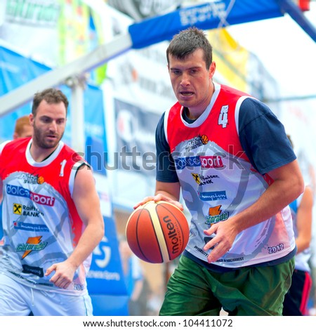 BUCHAREST, ROMANIA - MAY 20: Unknown bascketball  players performs during the game Sport Arena Streetball 3x3, Play On (red) vs. Tiki Taka Polit (blue) on May 20, 2012 in Bucharest, Romania - stock photo