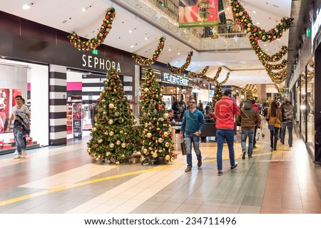 BUCHAREST, ROMANIA - NOVEMBER 30, 2014: People Shopping For Christmas In Luxury Shopping Mall Interior. - stock photo