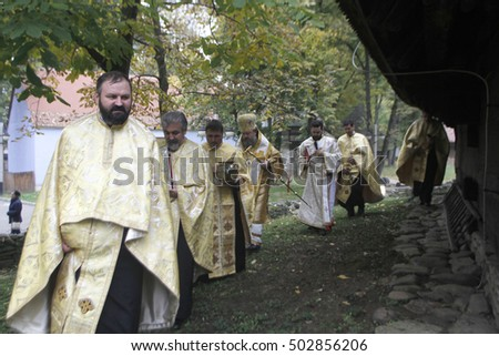 BUCHAREST, ROMANIA - OCTOBER 23, 2016:  Episcopal vicar Timotei Prahoveanul performs church sanctification of  a 18th century wooden church in National Village Museum.