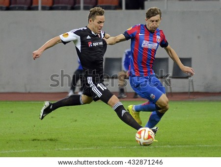 BUCHAREST, ROMANIA - SEPTEMBER 18, 2014: Anders Jacobsen and Cornel Rapa pictured during the UEFA Europa League game between Steaua Bucuresti and Aalborg on National Arena. - stock photo