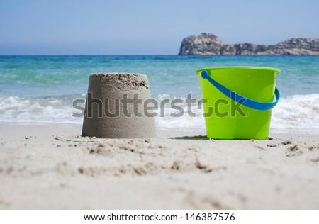 Bucket and sandcastle on a sandy beach - stock photo