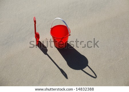 Bucket and spade on a beach to represent holidays - stock photo