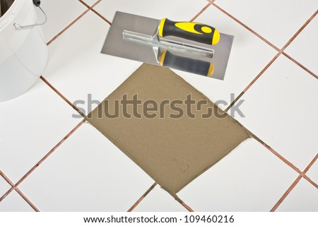 bucket and Trowel and old white tiles with tile adhesive - stock photo