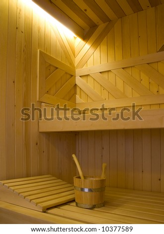 Bucket for water and two pillows on bench in Finnish sauna. - stock photo