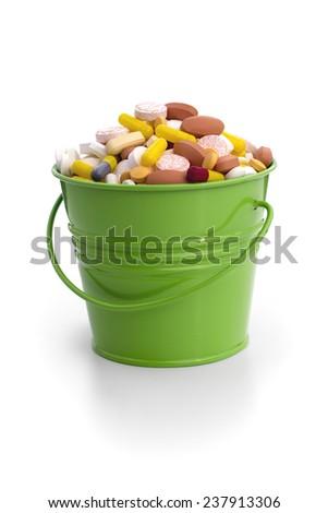 BUCKET FULL OF DRUGS 1 - Bucket full of pills and capsules. - stock photo