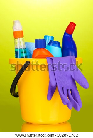 Bucket with cleaning items on green background - stock photo
