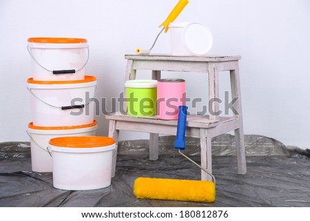 Buckets with paint and ladder on wall background. Conceptual photo of repairing works in  room