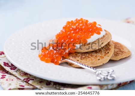 Buckwheat blini with red caviar and sour cream on white plate, selective focus - stock photo
