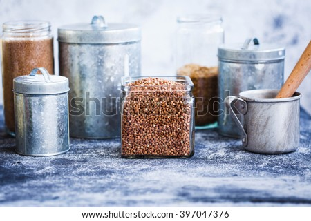 Buckwheat cereal glass jar and variety metallic storage jars on a kitchen country table. Healthy, detox and dieting food concept.  - stock photo