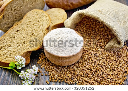 Buckwheat flour in a wooden bowl, buckwheat in the bag, slices of bread, buckwheat flower on the background of wooden boards - stock photo