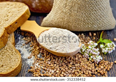 Buckwheat Flour in spoon, buckwheat in the bag on the table, slices of bread, buckwheat flower on the background of wooden boards - stock photo