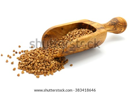 Buckwheat grains in wooden scoop on white isolated background
