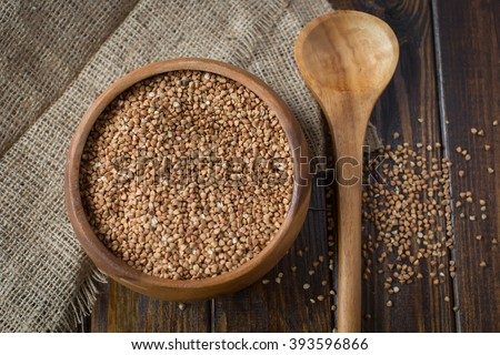 Buckwheat groats in a bowl and wooden scoop with buckwheat on gr - stock photo