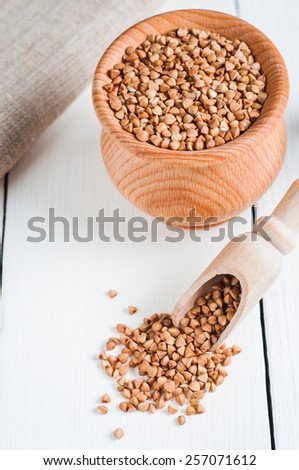 buckwheat in a wooden bowl on white background. View from above