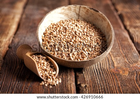 Buckwheat in scoop and bowl on wooden table - stock photo