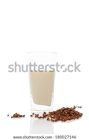 Buckwheat milk in glass with dry buckwheat seeds isolated on white background. Vegan and vegetarian milk concept. - stock photo